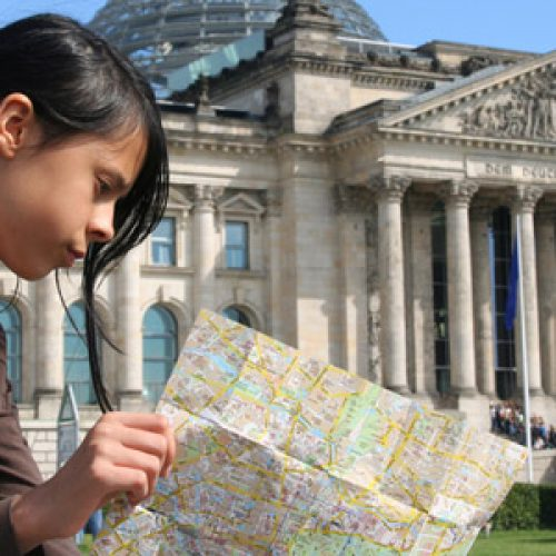 Berlin: Girl with map at Reichstag building. Focus on girl.